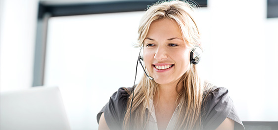 Smiling blonde woman wearing a headset and looking at a computer.