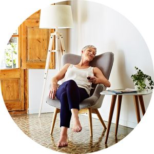 Older barefoot woman in a grey lounge chair holding glass of red wine.